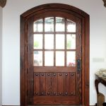 Arched entry with bubble glass and clavos