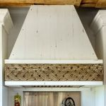 Stove hood with antique carved panel